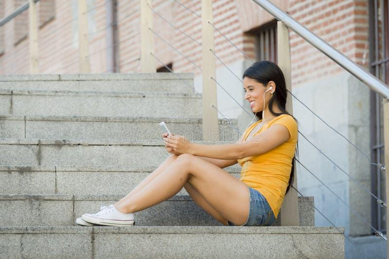 Mujer latina atractiva que escucha la música en su teléfono elegante fotos de archivo libres de regalías