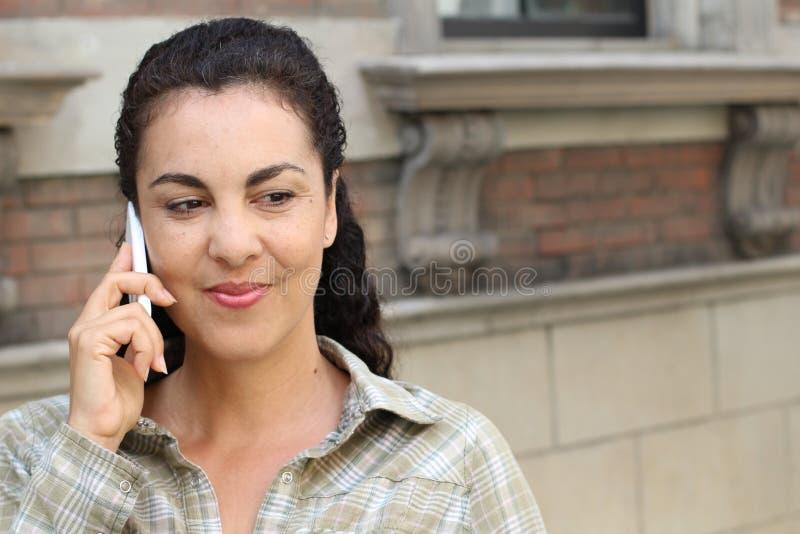 Mujer latina con la camisa de tela escocesa que llama por el teléfono en la ciudad imágenes de archivo libres de regalías