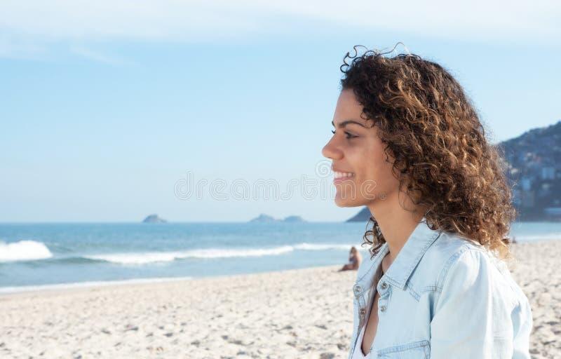 Mujer latina de risa en la playa y mirada al océano fotos de archivo