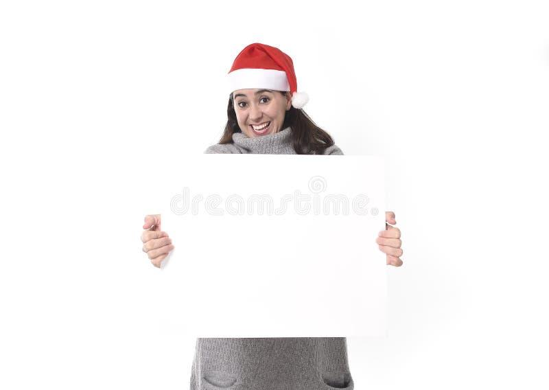 Mujer latina dulce joven en el sombrero de Santa Christmas que sostiene la cartelera en blanco como espacio de la copia foto de archivo libre de regalías