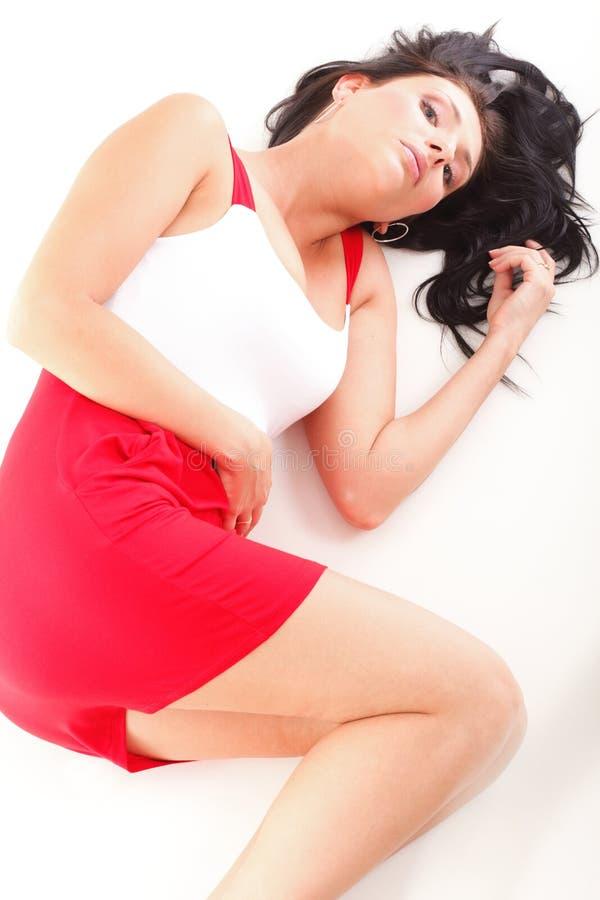 Mujer latina en la mentira roja en el blanco del piso imagen de archivo libre de regalías