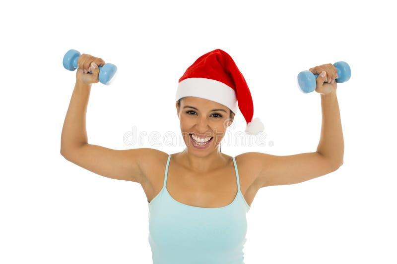Mujer latina en la ropa de la aptitud y el sombrero de la Navidad de Papá Noel que llevan a cabo pesos imagen de archivo libre de regalías