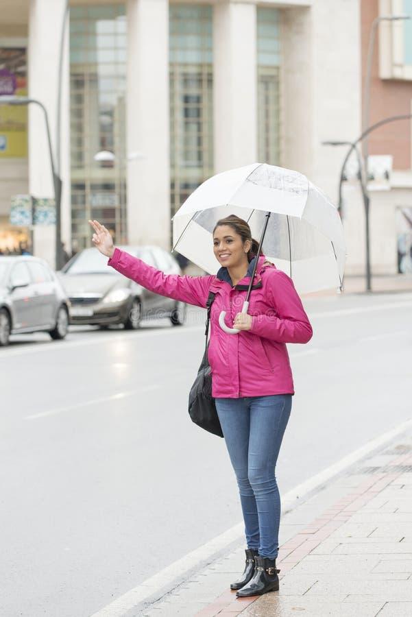 Mujer latina hermosa con el paraguas que hace autostop en la calle imagenes de archivo