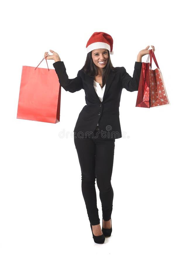 Mujer latina hermosa feliz con el sombrero de santa de la Navidad que sostiene los panieres de la venta excitados imagenes de archivo