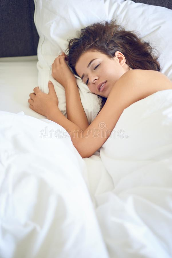 Mujer latina hermosa joven de la mujer con el pelo moreno largo que miente en su cama imagen de archivo libre de regalías