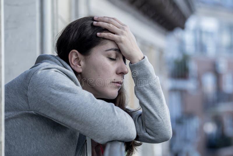 Mujer latina hermosa joven que parece triste y deprimida en un balcón en un concepto de la depresión fotos de archivo