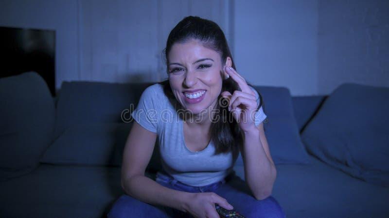 mujer latina hermosa y feliz joven en su 30s que sostiene el telecontrol de la TV que disfruta en casa del programa de televisión fotografía de archivo libre de regalías