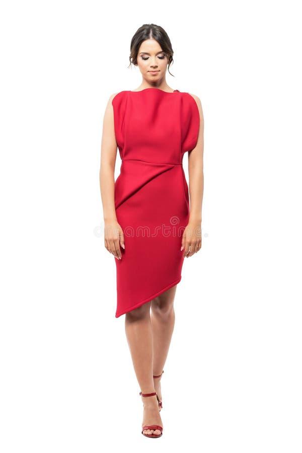 Mujer latina joven sofisticada en vestido rojo que camina y que mira abajo fotos de archivo libres de regalías