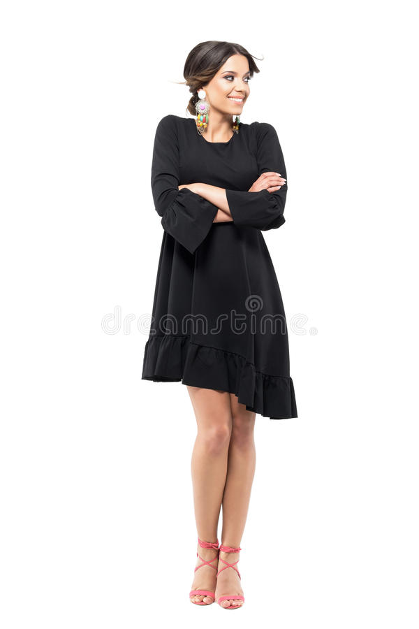 Mujer latina magnífica en el vestido negro que congela con los brazos cruzados y el pelo ventoso imagenes de archivo