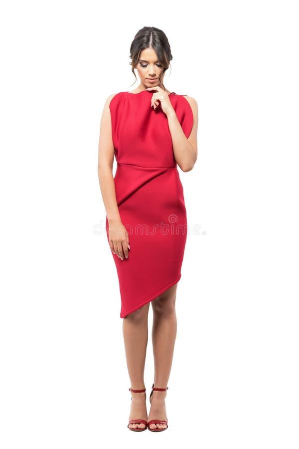Mujer latina pensativa triste en vestido rojo con el finger en la barbilla que mira abajo de pensativo fotografía de archivo