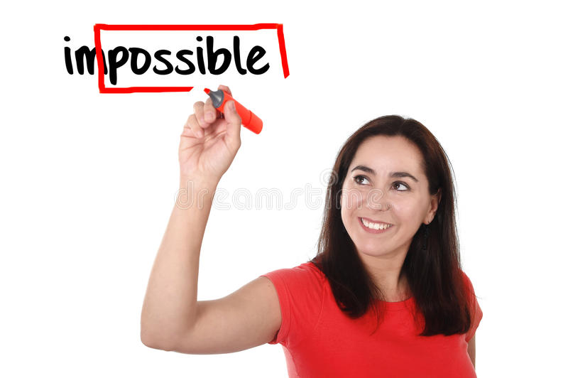 Mujer latina que da vuelta a palabra imposible en la escritura posible con el marcador rojo imágenes de archivo libres de regalías