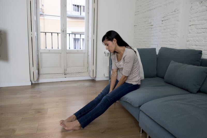 Mujer latina que miente en casa sentándose en la depresión sufridora preocupante gritadora del sofá que siente triste imagenes de archivo