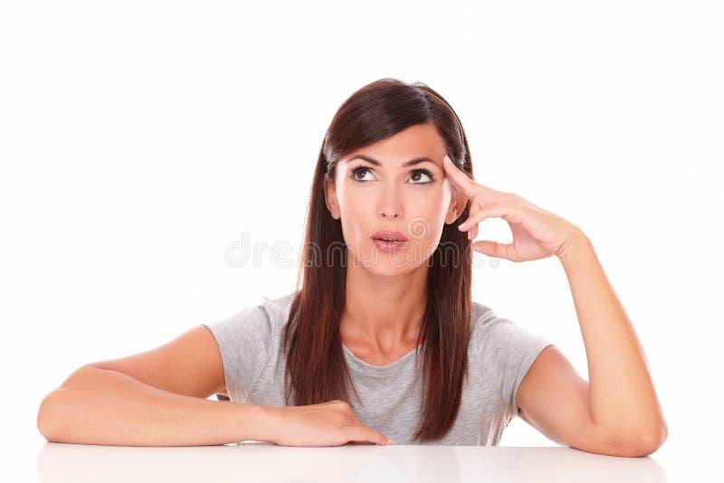 Mujer latina reflexiva que se pregunta mientras que mira para arriba imagenes de archivo