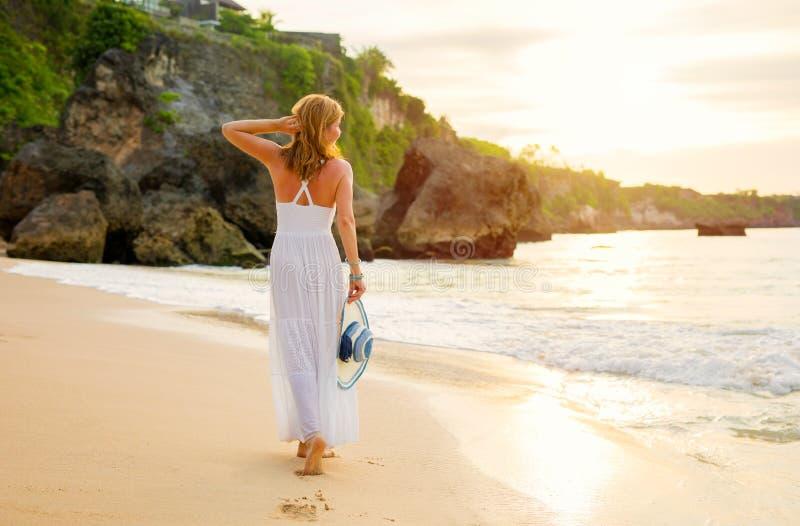 Mujer libre de la tensión en el vestido blanco del verano que camina en la playa en la puesta del sol imagen de archivo
