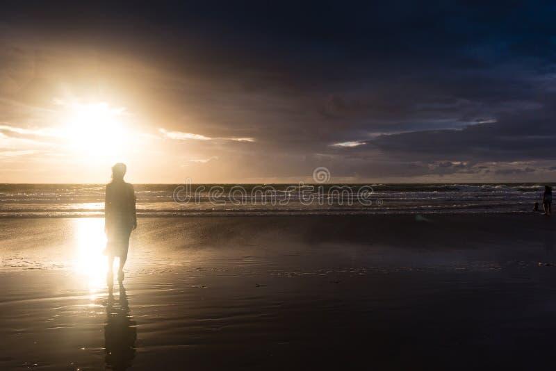 Mujer libre que disfruta de la libertad que siente feliz en la playa en la puesta del sol Mujer relajante serena hermosa en felic imagen de archivo libre de regalías
