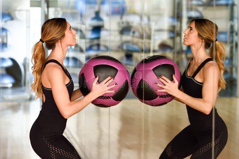 Mujer liftting con en el gimnasio fotos de archivo libres de regalías