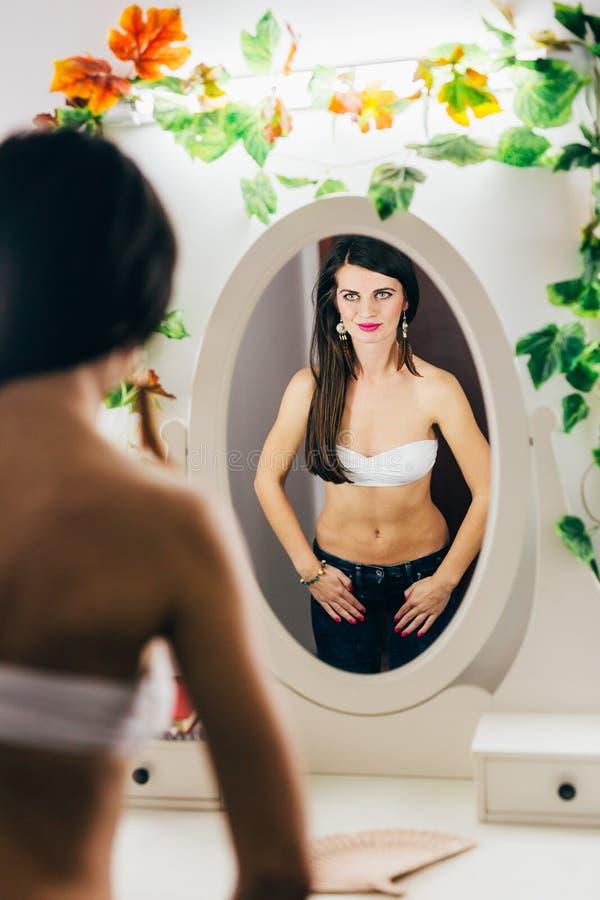 Mujer linda atractiva que mira en el espejo imagen de archivo libre de regalías