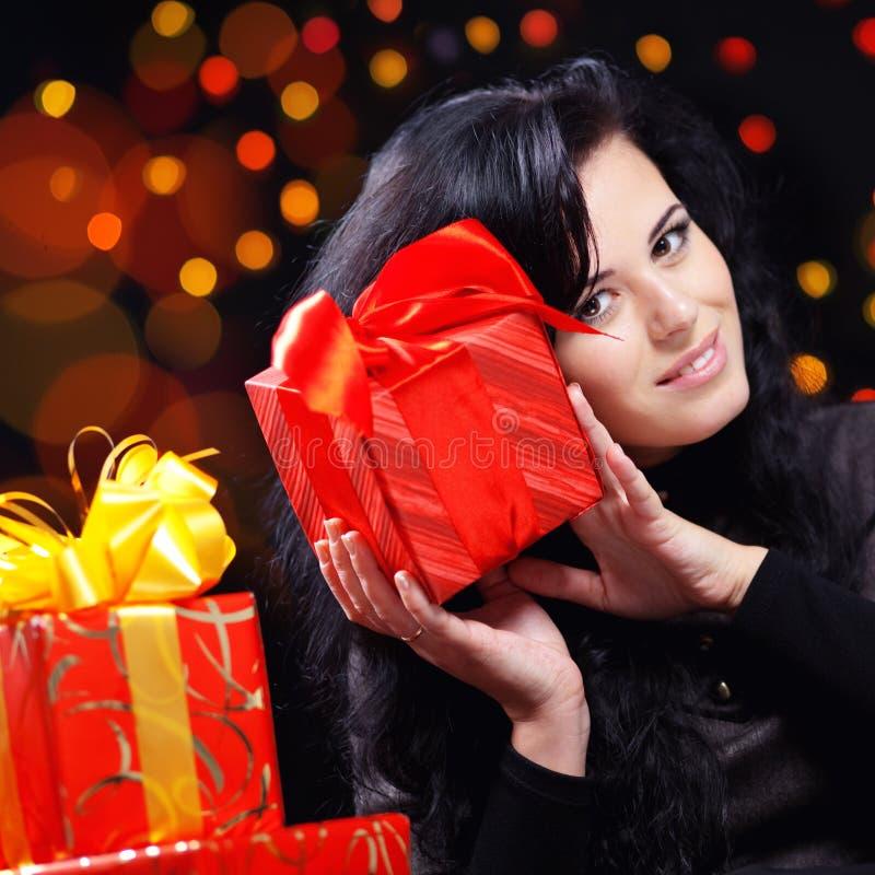 Mujer linda con los presentes en la noche imagen de archivo