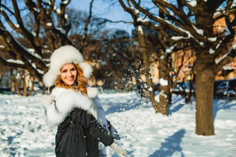 Mujer linda del invierno en el sombrero de piel que se divierte al aire libre imagen de archivo