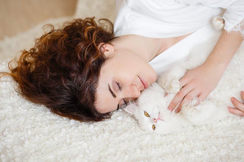 Mujer linda del pelo rizado en una bata de seda blanca en la madrugada que juega con el gato mullido blanco que se sienta en el s imagen de archivo libre de regalías