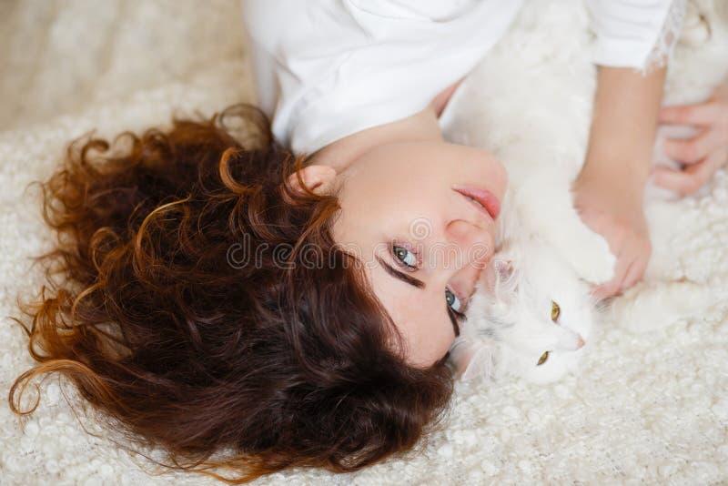 Mujer linda del pelo rizado en una bata de seda blanca en la madrugada que juega con el gato mullido blanco que se sienta en el s imagenes de archivo
