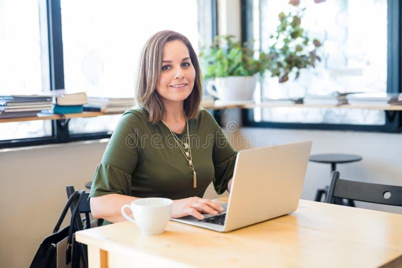 Mujer linda en el café con el ordenador portátil imágenes de archivo libres de regalías