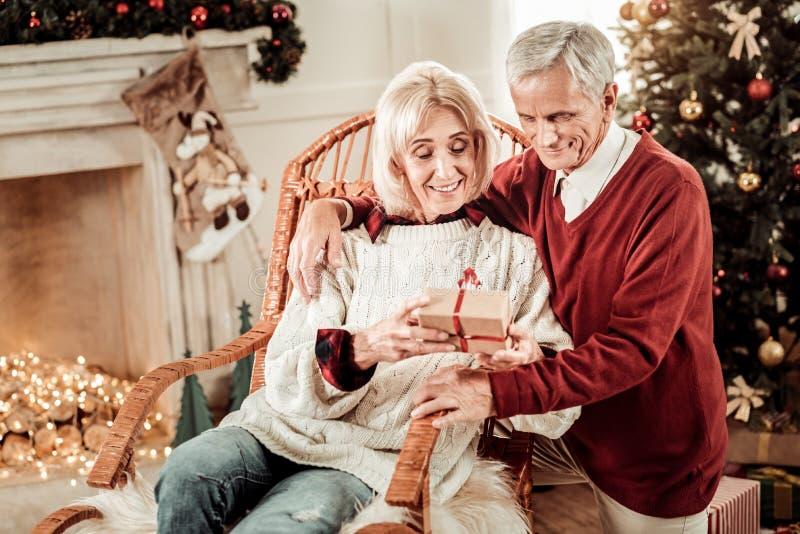 Mujer linda interesada que sienta y que sostiene un regalo foto de archivo