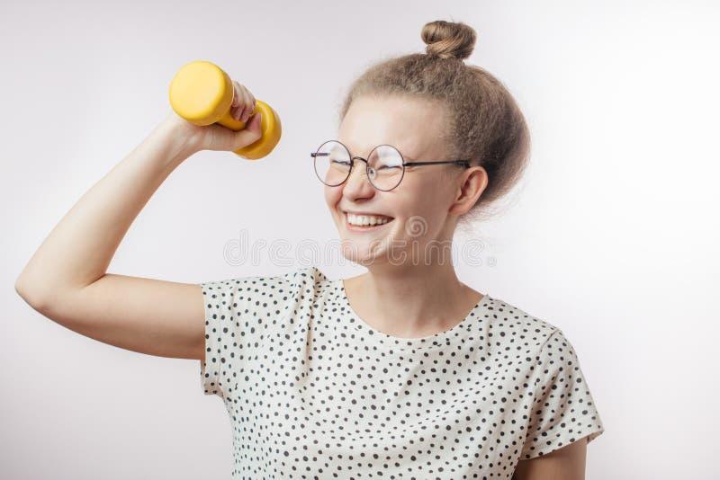 Mujer linda joven atractiva que ríe y que lleva a cabo el dumbell Tiro del estudio fotografía de archivo