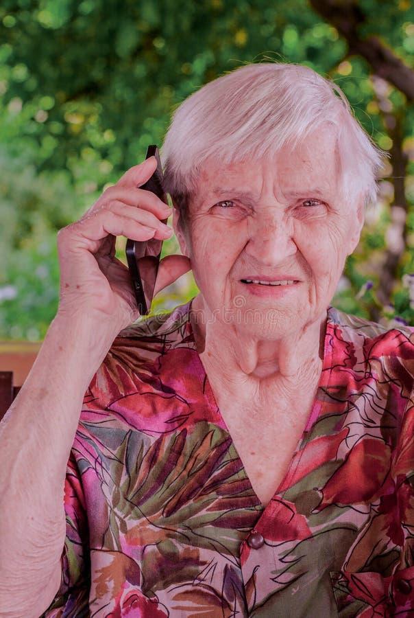 Mujer linda, mayor que habla en un teléfono móvil fotografía de archivo libre de regalías