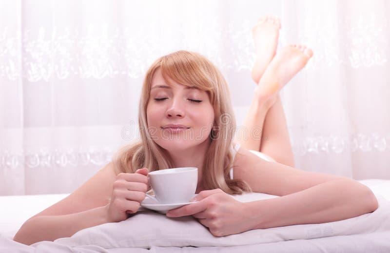 Mujer linda que bebe una mentira del café foto de archivo