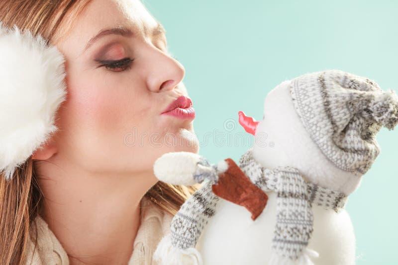 Mujer linda que besa al pequeño muñeco de nieve Moda del invierno imagen de archivo libre de regalías