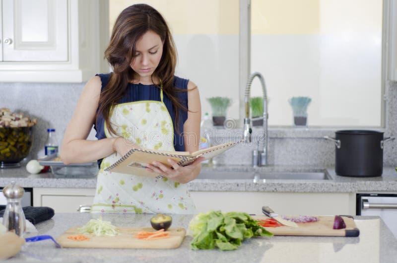 Mujer linda que cocina una receta imagenes de archivo