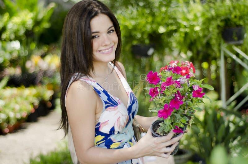 Mujer linda que compra algunas plantas imagenes de archivo