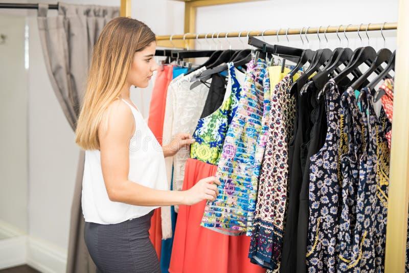 Mujer linda que compra un poco de ropa foto de archivo