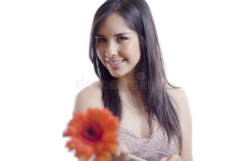 Mujer linda que da una flor lejos imagen de archivo