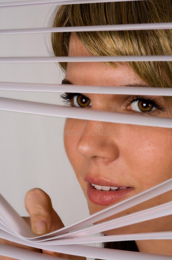 Mujer linda que mira a escondidas a través de persianas fotos de archivo