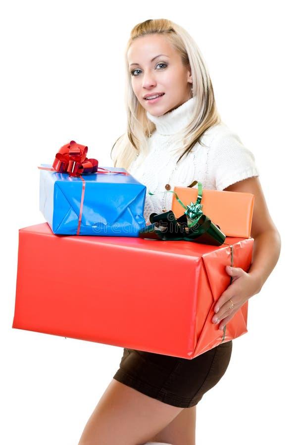 Mujer linda que se sostiene presente en el tiempo de la Navidad foto de archivo