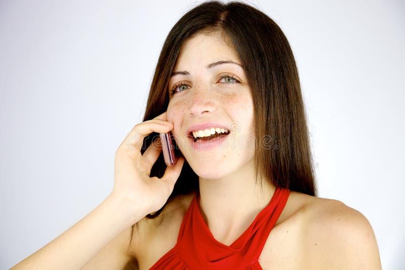 Mujer linda que sonríe en el teléfono feliz fotos de archivo libres de regalías