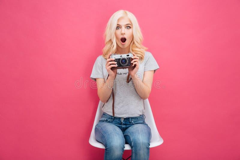Mujer linda que sostiene la cámara de la foto imagen de archivo
