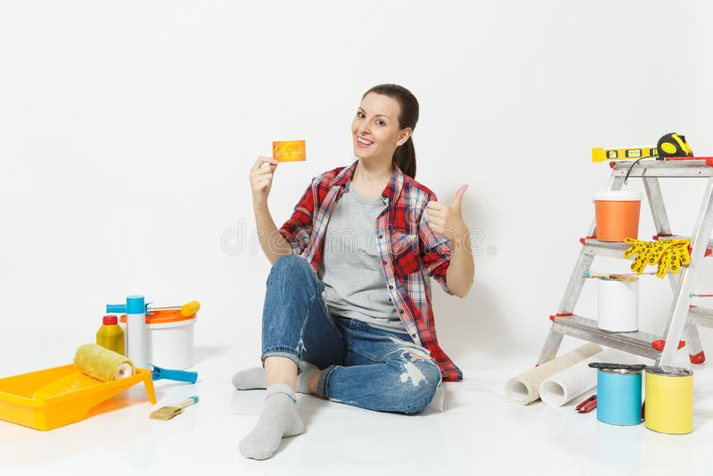 Mujer linda que sostiene la tarjeta de crédito con el dinero que se sienta en piso con los instrumentos para el apartamento de la imagen de archivo