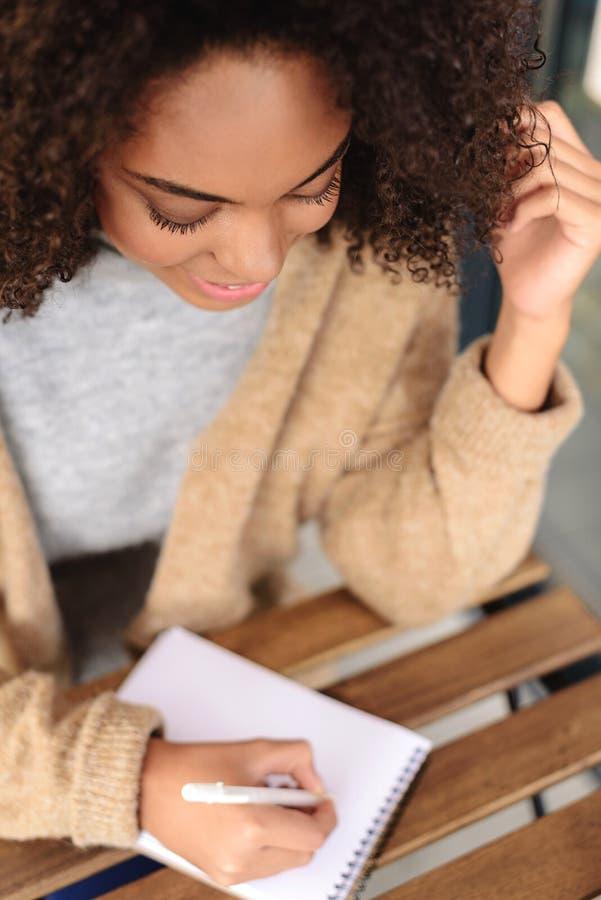 Mujer linda que toma notas dentro foto de archivo