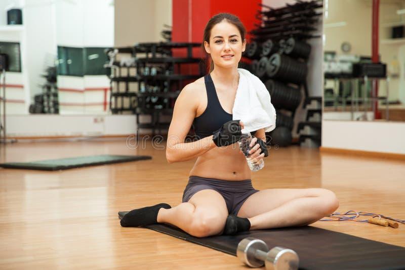 Mujer linda que toma una rotura en el gimnasio fotos de archivo libres de regalías