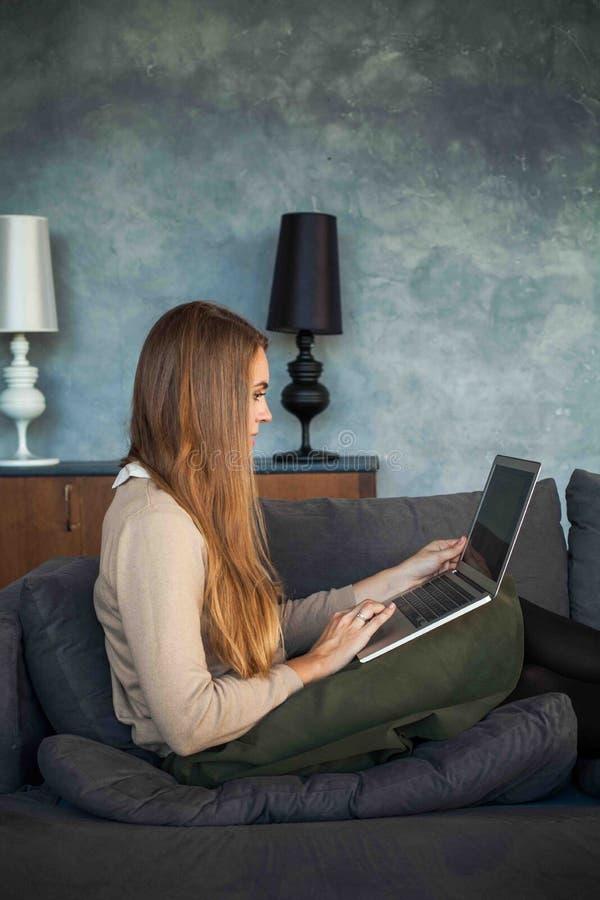 Mujer linda que trabaja en casa la oficina y que usa el ordenador portátil imagen de archivo
