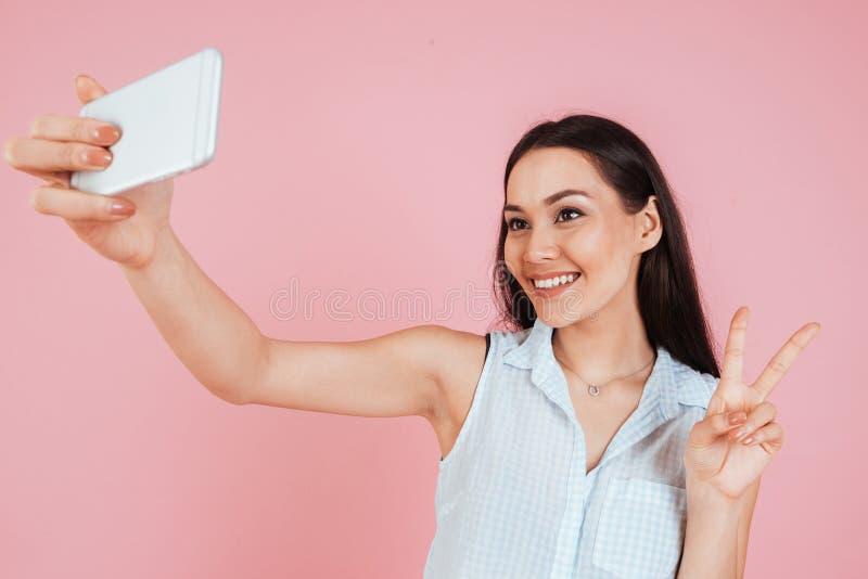 Mujer linda sonriente que hace la foto del selfie en smartphone foto de archivo libre de regalías