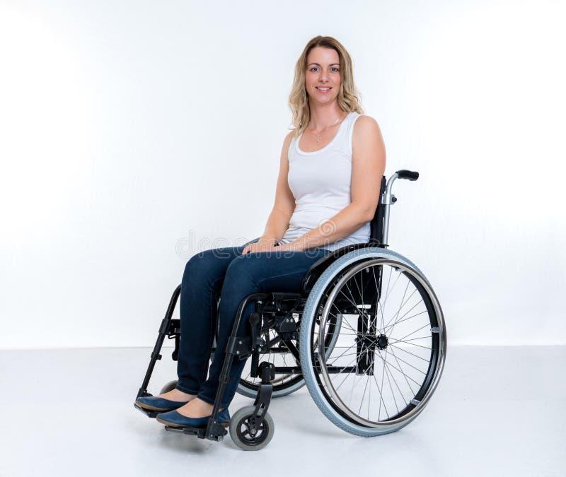 Mujer lisiada en sillón de ruedas imágenes de archivo libres de regalías