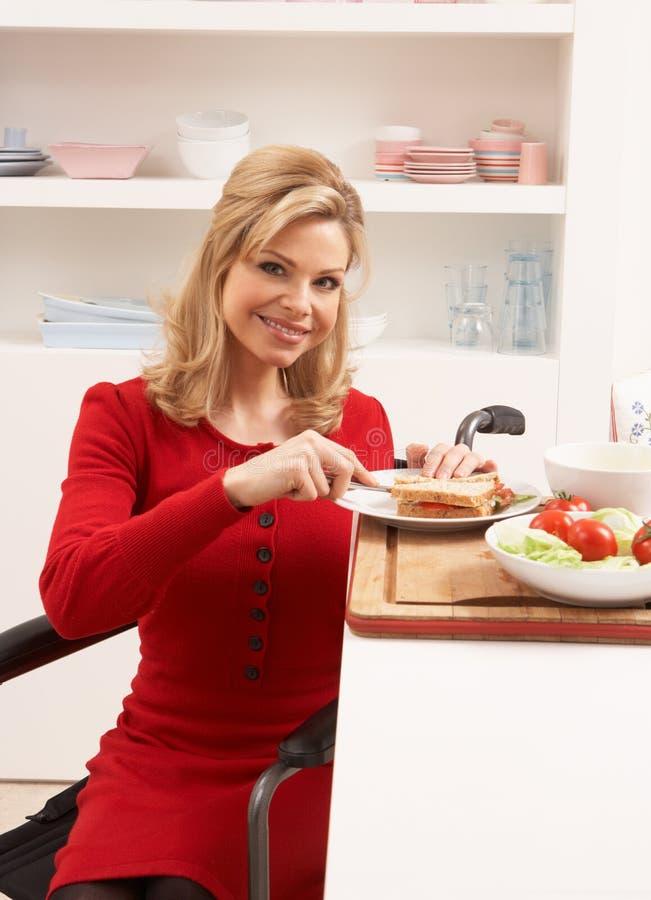 Mujer lisiada que hace el emparedado en cocina foto de archivo