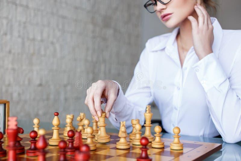 Mujer lista que se mueve con la reina en el tablero de ajedrez fotos de archivo