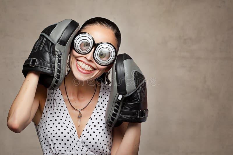 Mujer loca divertida con los ojos, los vidrios y los guantes de boxeo grandes foto de archivo