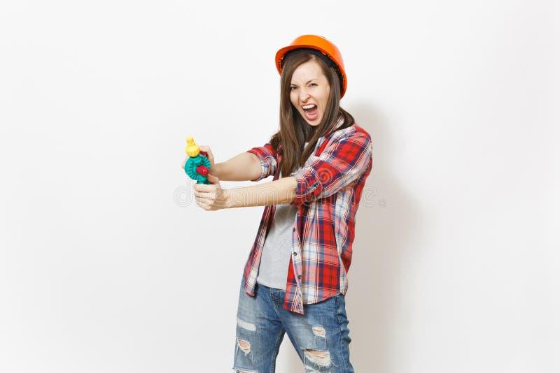 Mujer loca irritada en ropa casual y el taladro anaranjado del juguete de la tenencia del casco de la construcción protectora ais fotos de archivo libres de regalías