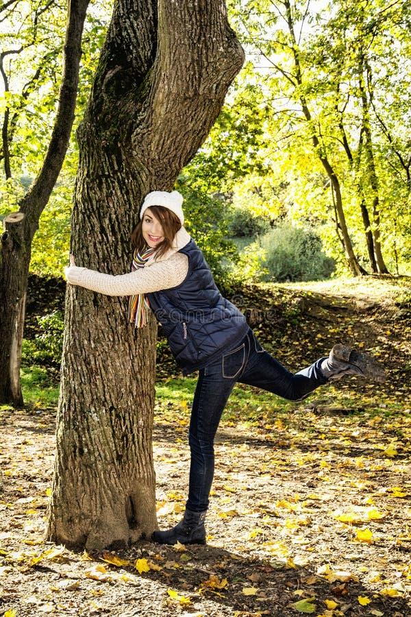 Mujer loca joven que abraza el árbol en otoño al aire libre fotos de archivo libres de regalías